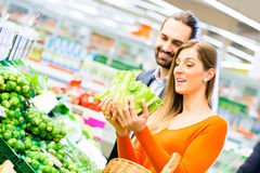 couple-shopping-groceries-supermarket-selecting-vegetables-grocery-40899218