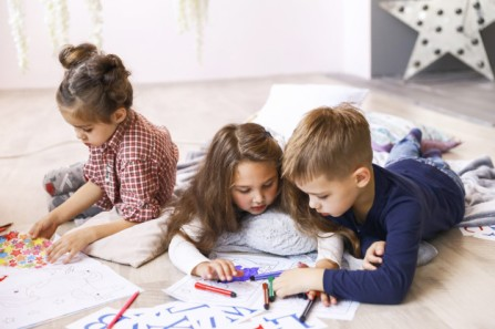 three-focused-children-are-playing-floor-drawing-coloring-books_8353-10845