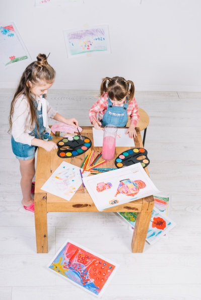 two-little-girls-painting-with-aquarelle-paper-table_23-2148037802