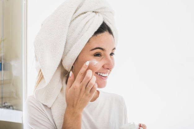 happy-portrait-young-woman-applying-cream-her-face_23-2148161298